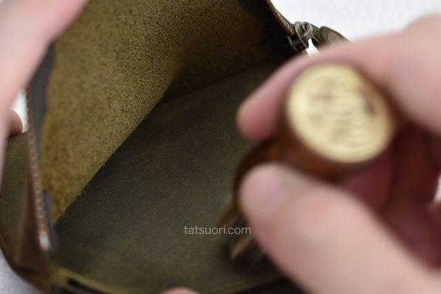 財布の奥の届きにくいところのゴミやホコリを取り除いている「コロニル アプリケーションブラシ」